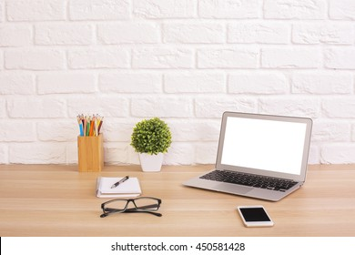 Front view of creative designer desktop with blank white laptop, cell phone, glasses, plant and stationery items on white brick wall background. Mock up