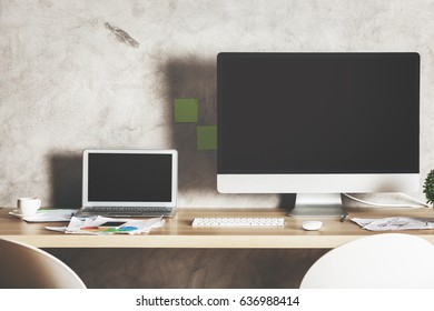 Front view of creative designer desktop with large blank white computer screen, laptop and supplies. Shadow on concrete wall. Mock up