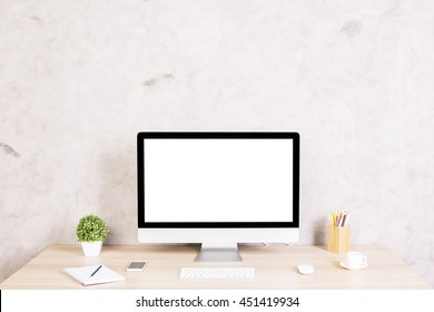 Front view of creative hipster desktop with blank white computer screen, coffee cup, smart phone and other items on concrete background. Mock up