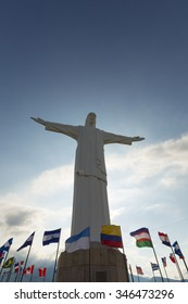 Front view of Cristo del Rey statue of Cali against a blue sky with international flags waving around. Colombia