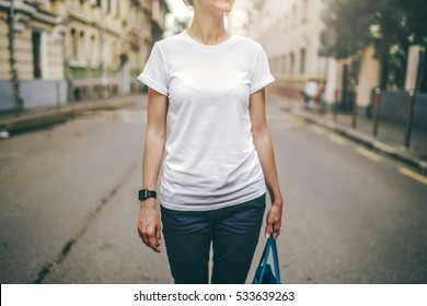 Front view. Cropped image. Summer day, a young woman in a white t-shirt standing on a city street. Wristwatch on the hand of the girl. Blurred background. Advertising space, mock up