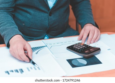Front view of Cropped picture businessman working on desk office  financial graph with using a calculator to calculate the numbers,accounting investment and finance concept.