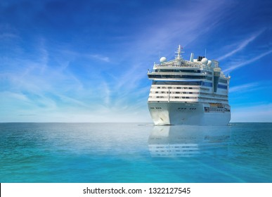 Front view Cruise ship sailing in the sea, large luxury white cruise ship liner on blue sea water and cloudy sky background.