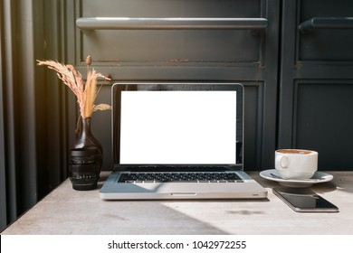 Front view of cup coffee,smartphone and laptop on table in office and background black