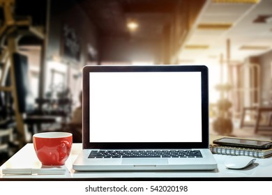 Front view of cup and laptop on table in Office in fitness gym in morning light