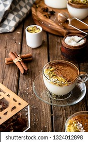 front view for a cup of Sahlab,  Arabic pudding hot drink, decorated with cinnamon and coconut, on rustic old wooden table