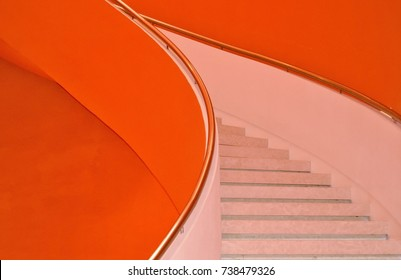 Front view of curving classical staircase with orange wall as background with space for copy