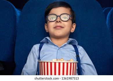 Front view of cute, little boy enjoying movie premiere. Cheerful kid watching film or cartoon, sitting in comfortable dark blue chair, holding popcorn bucket.