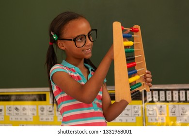 Front view of a cute mixed-race schoolgirl learning mathematics with abacus in the classroom at school