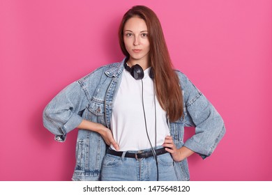 Front view of dark haired woman dressed denim jacket, jeans and t shirt, standing with hand on hips, having serious facial expression, waits her boyfriend from party, model posing isolated on pink.