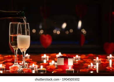 Front view of Valentine's Day romantic scene with gift, candles, petals of red roses, chimney fire and glasses of champagne. Concept about lifestyle, love and celebrations. Copy space on top.