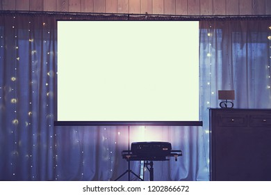 Front view of decorated wedding room with empty white projector screen in the centre. Equipment for video and slideshow projection at a festive event. Banquette hall with a board for projection
