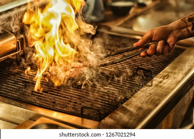 Front view of delicious juicy steak flaming with fire and smoke on grill. Hand of professional chef turning over steak. Concept of culinary and restaurant food and kitchen.