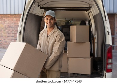 Front view of delivery man carrying cardboard boxes on trolley near van outside the warehouse. This is a freight transportation and distribution warehouse. Industrial and industrial workers concept