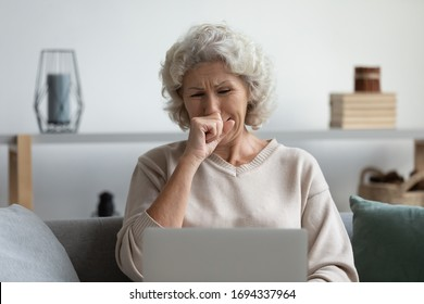Front view depressed senior older woman crying, looking at computer screen. Stressed worried middle aged mature grandmother grieving, received bad message notification, sitting alone at home.