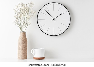 Front view desk with round wall clock, cup and flower in bottle vase on white background. Home office minimal workspace desk