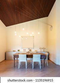 Front view dining room with wooden ceiling. Modern chandelier.