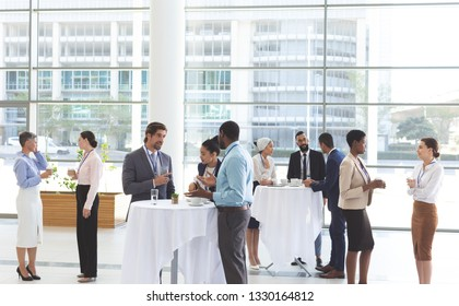 Front view of diverse business people interacting with each other at table after a conference in office lobby