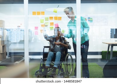 Front view of diverse executives discussing together over sticky notes in office. This is a casual creative start-up business office for a diverse team