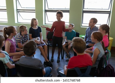 Front view of a diverse group of elementary school kids sitting on chairs in a circle and interacting during a lesson, one African American girl standing and talking while her classmates and male