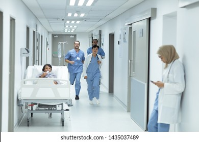 Vista frontal de diversos equipos médicos corriendo en el pasillo del hospital
