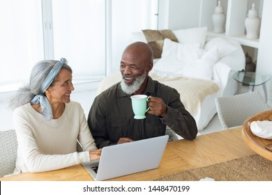 Front view of diverse senior couple using laptop on table while man holds a cup in beach house. Authentic Senior Retired Life Concept