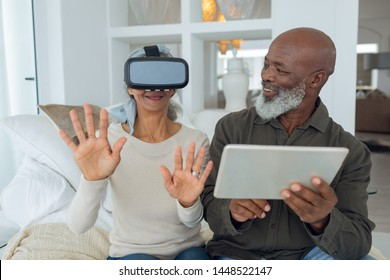 Front view of diverse senior couple using digital devices while sitting inside a room in beach house. Authentic Senior Retired Life Concept