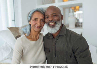 Front view of diverse senior couple smiling while sitting on a couch inside a room in beach house. Authentic Senior Retired Life Concept
