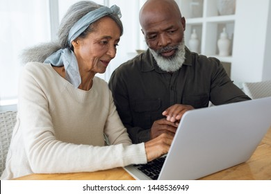 Front view of diverse senior couple using laptop on table inside a room in beach house. Authentic Senior Retired Life Concept