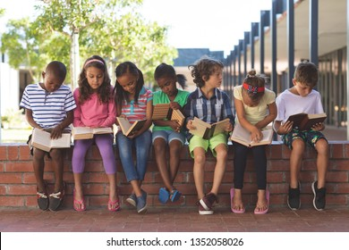Front view of diverse students reading book while sitting on brick wall at corridor in school