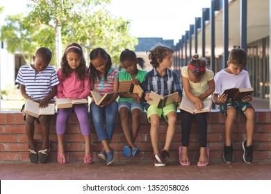 Vorderansicht verschiedener Schüler, die in der Schule auf Ziegelwand sitzen