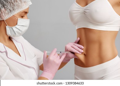 Front view of doctor doing injection in naked abdoman of client. Beautiful naked figure of woman getting anti cellulite and rejuvenating procedures, making her skin lifted and perfect.