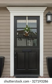 front view of front door with black wood, a chair with mailbox and doorbell