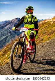 Front view of downhill bicyclist standing with full-suspension mountain bike at sunny summer day