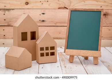 FRONT view of empty blackboard with room for text and house shaped paper cut over wooden table