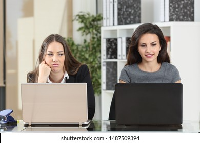 Front view of an envious employee looking her colleague working beside