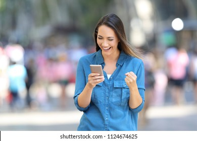 Front view of a excited woman reading good news in a smart phone online on the street