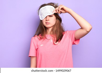 Front view of exhausted young woman raises slightly her eye mask, trying to open sleepy eyes, needs more rest after hard week, out of energy, hates morning. Sleep and wake up concept.