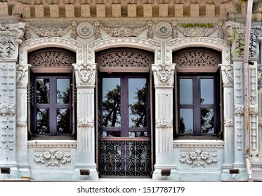 Front view of exterior of traditional Straits Chinese or Peranakan vintage shop house with antique brown wooden shutters and white facade in Kampong Glam Singapore