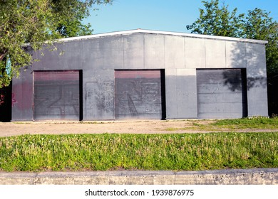 Front view of the facade of a large dark hangar structure with three closed doorways