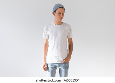 Front view or face side of young hipster millennial man, skinny and fit with arm tattoos, natural handsome beauty in white simple mockup tshirt from organic cotton
