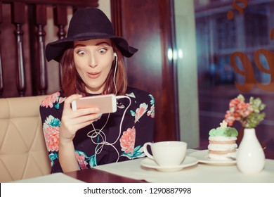 Front view of a fashion girl amazed shocked woman checking smart phone in coffee shop face looking at cellphone towards camera. Girl received shocking good news or amazing deals online in social media