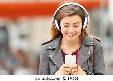 Front view of a fashion girl listening music with headphones and smart phone on line and walking towards camera in the street