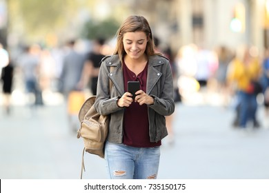 Front view of a fashion girl walking and texting on a smart phone on the street
