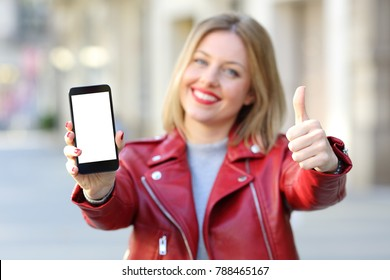 Front view of a fashion happy woman showing a smartphone blank screen with thumbs up on the street