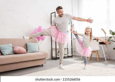 front view of father and daughter in tutu skirts standing on one leg