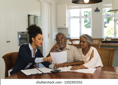 Front view of a female African American  real estate agent and senior couple discussing over documents at the table of the living room at home
