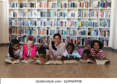 Front view of female teacher and schoolkids reading a book while lying on floor of school library