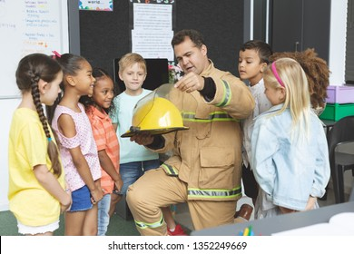 Front view of firefighter teaching student about fire safety while holding fire helmet