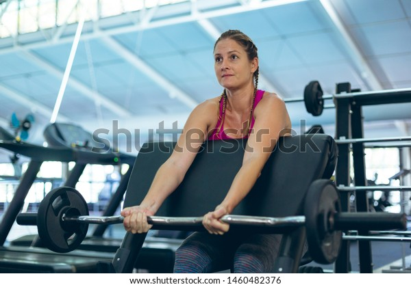 Front view of fit young Caucasian female athletic exercising with barbell on preacher bench in fitness center. Bright modern gym with fit healthy people working out and training